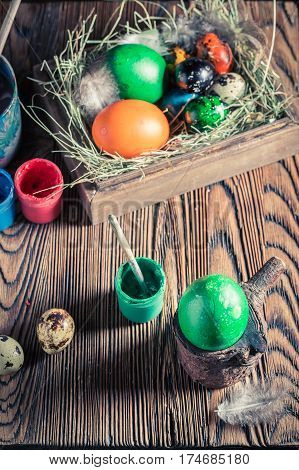 Painting Eggs For Easter With Hay And Feathers