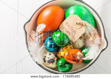 Various Eggs For Easter With Feathers On Pan