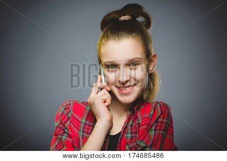 Closeup Portrait of happy girl with mobile or cell phone on gray background.