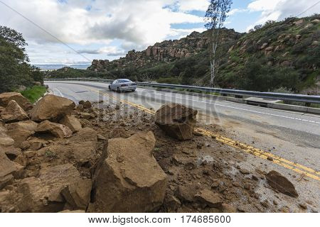 Los Angeles, California, USA - February 18, 2017:  Car passing storm caused rock slide on Santa Susana Pass Road in the San Fernando Valley.