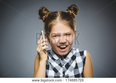 Portrait of offense girl with mobile or cell phone. Negative human emotion, facial expression. Closeup.
