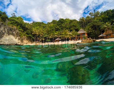 Tropical beach with green trees and bungalow resort. Romantic vacation place. Double landscape with sea water and coast. Tropical seashore view in sunny day. Perfect place for vacation. Holiday banner