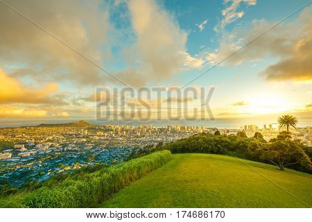 Tantalus Lookout at sunset, Puu Ualakaa State Park Honolulu. Tourists on panoramic city, Waikiki Beach and Diamond Head. Waikiki skyline Oahu Hawaii, United States. Vacation and travel concept.