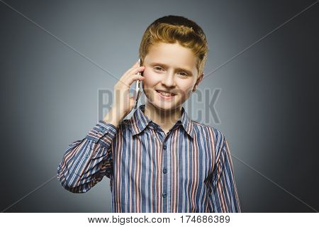 Closeup Portrait of happy boy with mobile or cell phone on gray background.
