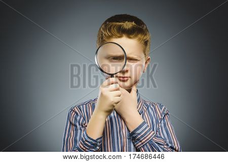 Boy See Through Magnifying Glass, Kid Eye Looking with Magnifier Lens over Gray.