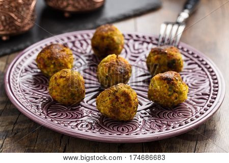 Homemade couscous and vegetable balls served on a decorative plate.