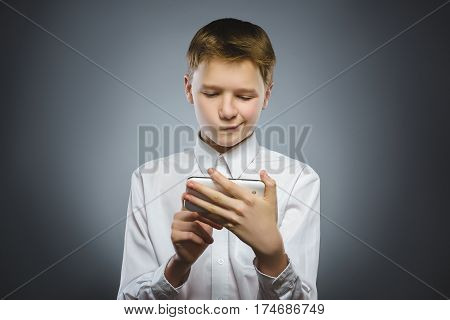 Portrait of offense boy with mobile or cell phone. Negative human emotion.