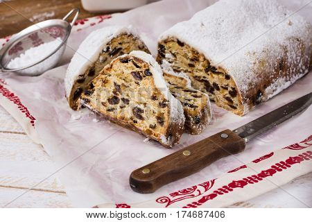 German Christmas stollen with cut off slices on waxed paper over linen ornamemnted towel knife sieve with powdered sugar