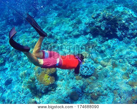 Snorkeling man dives to sea bottom. Young coral reef in deep blue water. Modern snorkeling gear - full-face mask long fins swimsuit. Snorkeler in tropical lagoon underwater photo. Active holiday