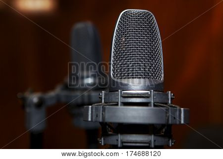 black condenser microphone in studio for singers