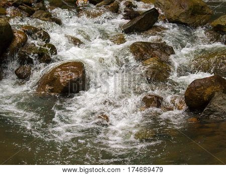 Fresh water river among black rocks. Fresh aqua fast stream in stones. Forest river with clean cold water. Fresh spring in mountains. Natural drinking water concept. Fast water current in wild nature