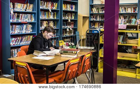 Library concept. University male student studying with books in library, Young student sitting in the library with books and reading, Schoolboy in the library. Library, teenager reading a book. librarian