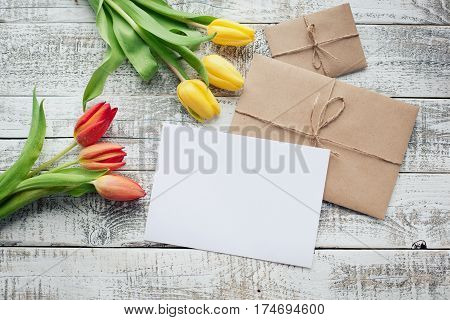 Yellow And Red Tulip Bouquet And Blank Greeting Card. Top View Over Wooden Table