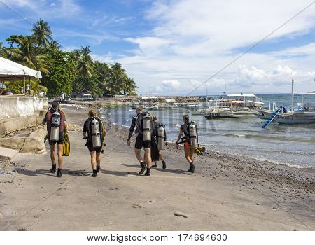 Dauin Philippines - 26 June 2016: The divers after the sea dive. Five young people in diving costumes on sand beach. Tropical nature landscape with divers. Sport on vacation