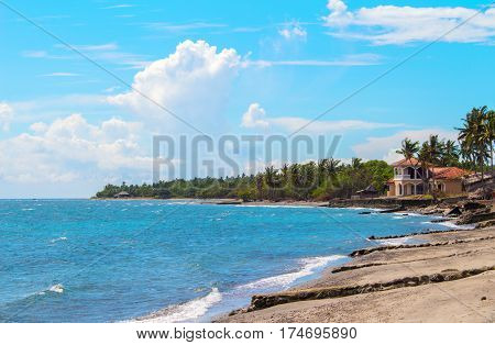 Tropical landscape with sea beach and palm tree. Sand beach view with palms and house. Tropical paradise landscape. Exotic island vintage photo. Simple life by sea. Romantic seaside