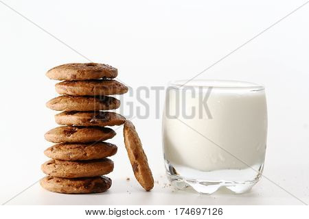 Chocolate Chip cookie with milk / A cookie is a baked or cooked good that is small, flat, and sweet, usually containing flour, sugar and some type of oil or fat