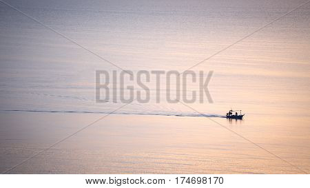 Minimal silhouette aerial view of fishery boat sail alone on calm sea at sunrise