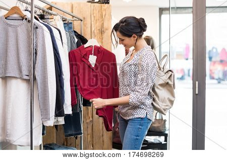 Happy young woman choosing a red blouse from a shop. Young woman in casuals with backpack checking the quality of blouse she is willing to buy. Happy girl buying new clothes for wardrobe.