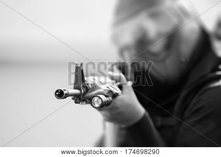 tactical rifle with flashlight of police in tactical suit aiming to target in black and white tone