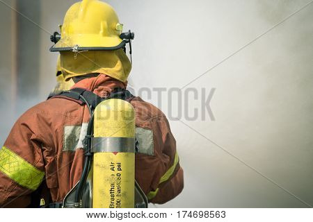single firefighter fire fighting suround with dark smoke in cinematic tone