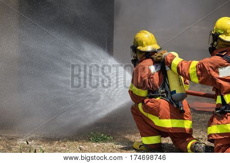 firefighter team water spray by high pressure fire hose with copy space