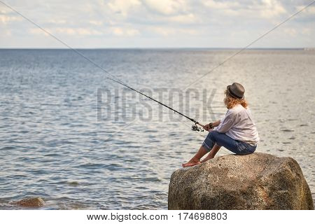 woman fisher sitting on summer sea beach