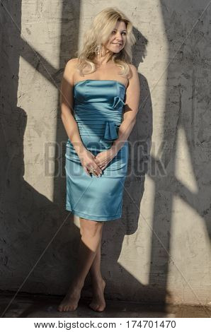 Girl blonde actress in a beautiful cocktail dress with open shoulders