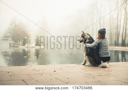 Image of young girl with her dog, alaskan malamute, outdoor at winter. Domestic pet. Husky.