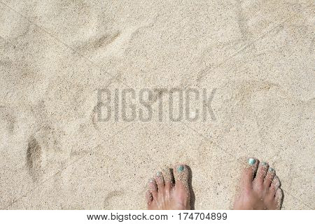 Female feet on white sand. Coral beach by the tropical seaside. Summer vacation in paradise banner template. Pedicure feet of woman on white sand beach. Sunny day on exotic island. Hawaii or Caribbean