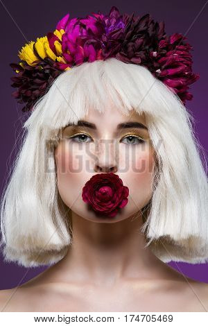 Beautiful young woman in blond wig with flowers on head and rose in mouth over dark background. Closeup beauty portrait. Copy space.