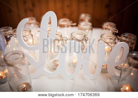 The word LOVE on white cloth around burning candles. Handmade.