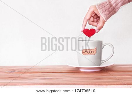hand holding red heart shape put into a Coffee cup mug with happy word tag on wooden table Romance and love valentines day background . Happy and relax concept