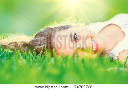 Beautiful teenage Girl lying on field of green grass close-up over sunlight. Outdoors. Model young woman smiling and enjoying nature outdoors. Cute Teenage Girl relaxing in park. Sunshine, Springtime