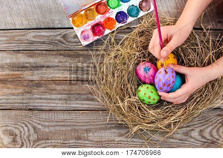 Girl paints Easter eggs on wooden background