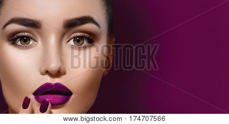 Beauty Brunette Woman with Perfect dark Makeup. Beautiful Professional Holiday Make-up. Deep violet color of Lips and Nails, perfect eyebrows. Beauty Girl's Face isolated on burgundy color background