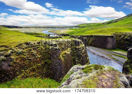The striking canyon Fyadrarglyufur in Iceland. Green Tundra in July. The concept of active northern tourism. Bizarre shape of cliffs and stream with glacial water