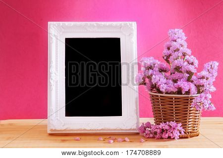 The White vintage photo frame with sweet statice flower in basket with blank wooden label on red pink background and wooden table romance concept