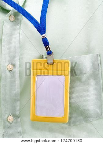 yellow plastic case of neck label hanging on green shirt pocket,  blank label for your simple text