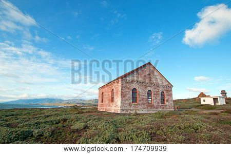 Red Brick Fog Signal Building under cumulus cloudscape at the Piedras Blancas Lighthouse on the Central California Coast USA