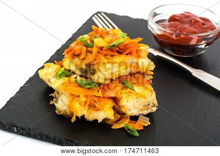 Greek style roast fish on black stone plate. Studio photo