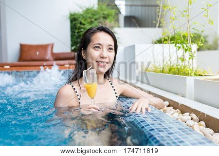 Young Woman enjoy her drink in swimming pool