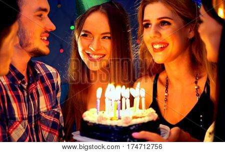 Happy friends birthday celebrating food with candle celebration cakes in club. People wear in hat party looking at burning candles. Women and men have fun.