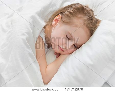Sweet girl napping, dreaming of something, hand under her hand, soft warm white blanket