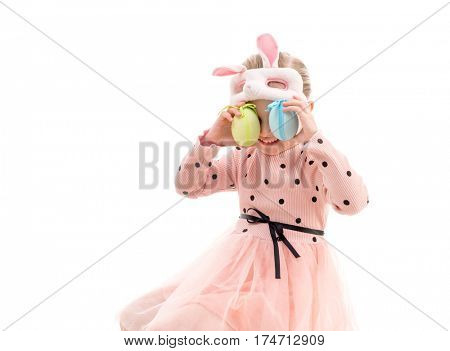 Sweet girl in polkadot dress and easter bunny mask holding eggs to her eyes, isolated