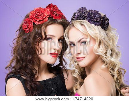 Beauty portrait. Couple of attractive blond and brunette girls with curly hair and a beautiful headband over purple background.