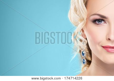 Half part portrait. Beautiful blond girl with luxury golden necklace over cyan background.