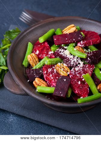 Vegetarian beetroot salad with geen beans, pecans, red oranges