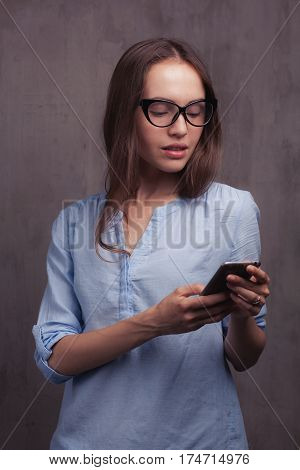 Closeup portrait of beautiful happy young woman with glasses chats by cellphone near grey background grunge wall