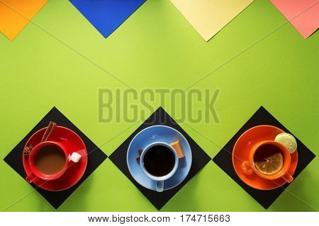 cup of coffee, tea and cacao at colorful paper background