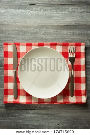 plate, knife and fork on rustic wooden background
